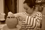 Janet is focused while molding a clay vase.