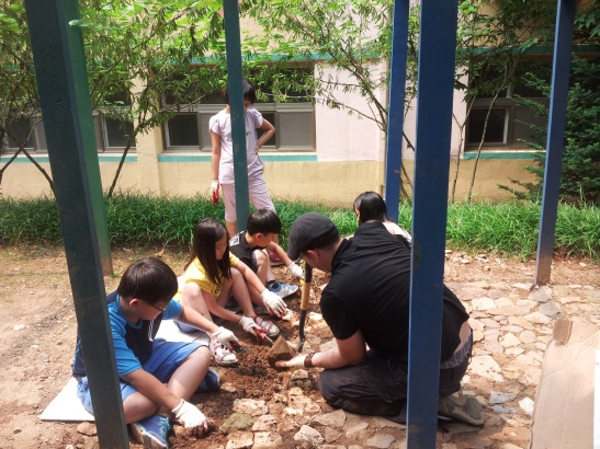 Students and I digging and packing dirt underneath and around rocks.